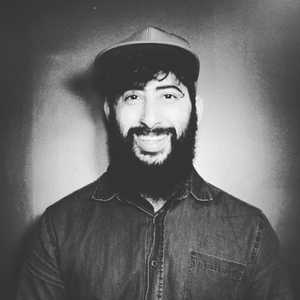 Roger Ramos grayscale profile photo with a nice smile and hat